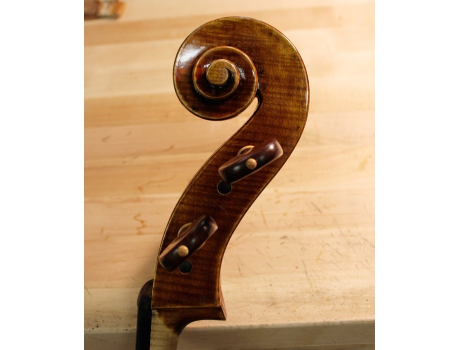 Finished cello scroll with pegs.